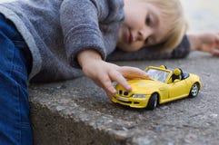 Weinig jongensspel met een auto Royalty-vrije Stock Afbeeldingen