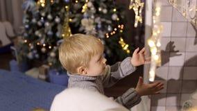 Weinig jongensspel met Kerstmisspeelgoed dichtbij open haard stock video