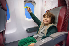 Weinig jongensspel met stuk speelgoed vliegtuig die aan vakantie vliegen Stock Foto