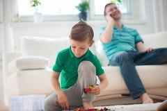 Weinig jongensspel, vader met telefon Royalty-vrije Stock Foto's