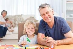 Weinig jongenstekening met zijn grote vader Stock Foto's