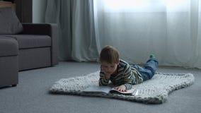 Weinig jongenstekening terwijl thuis het liggen op vloer stock videobeelden