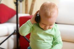 Weinig jongensvraag door draadloze telefoon thuis Royalty-vrije Stock Afbeelding