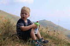 Weinig jongenszitting aan de heuvelpartij die de het drinken fles houden Royalty-vrije Stock Afbeelding