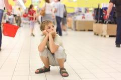 Weinig jongenszitting alleen op hunkers in grote opslag Stock Foto