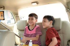 Weinig jongenszitting in auto het reizen stock foto