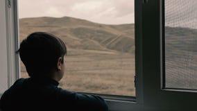 Weinig jongenszitting dichtbij het venster stock videobeelden