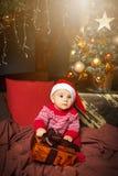Weinig jongenszitting en holding huidig in Santa Claus-hoed Royalty-vrije Stock Fotografie