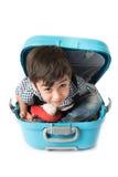 Weinig jongenszitting in koffer veronderstelt om te reizen royalty-vrije stock afbeelding