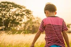 Weinig jongenszitting met gouden de zonsondergangtijd van het grassengebied royalty-vrije stock fotografie