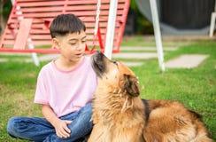 Weinig jongenszitting met hond stock afbeelding