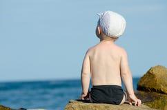Weinig jongenszitting met van hem terug naar een rots op de kust in zwembroek, blauwe hemel Royalty-vrije Stock Foto