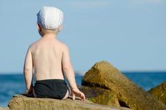 Weinig jongenszitting met van hem terug naar een rots op de kust in zwembroek, blauwe hemel Royalty-vrije Stock Afbeelding