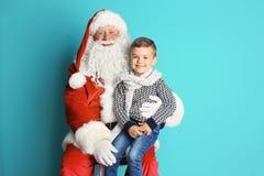 Weinig jongenszitting op authentieke Santa Claus Stock Foto's