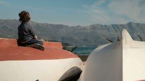 Weinig jongenszitting op boot, die ver dichtbij overzees in openlucht kijken stock video