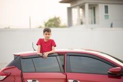 Weinig jongenszitting op de achterdeur van de auto met en de golf royalty-vrije stock fotografie