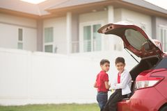 Weinig jongenszitting op de achterdeur van de auto met golf stock fotografie