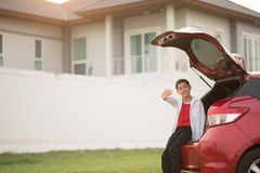 Weinig jongenszitting op de achterdeur van de auto met golf stock afbeeldingen