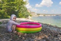 Weinig jongenszitting op de kust en het spelen in de opblaasbare pool op de achtergrond van een schilderachtig landschap royalty-vrije stock afbeelding