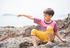 Weinig jongenszitting op de rots op het strandgezicht kijkt gelukkig Stock Foto's
