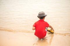 Weinig jongenszitting op de rots op het strandgezicht kijkt gelukkig Royalty-vrije Stock Foto's