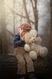Weinig jongenszitting op een boom en het koesteren van teddy Stock Afbeeldingen