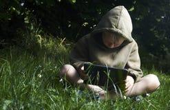 Weinig jongenszitting op gras en het gebruiken van tabletcomputer Royalty-vrije Stock Foto