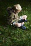Weinig jongenszitting op gras en het gebruiken van tabletcomputer Stock Foto