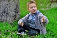 Weinig jongenszitting op groen gras royalty-vrije stock foto's