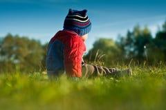 Weinig jongenszitting op het gras royalty-vrije stock afbeelding