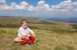 Weinig jongenszitting op het gras en het spelen met auto's op de achtergrond van een schilderachtig landschap die het overzees ov stock foto's