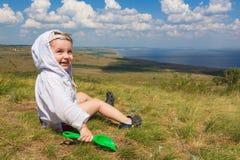 Weinig jongenszitting op het gras en het spelen met schop op de achtergrond van een schilderachtig landschap die het overzees ove royalty-vrije stock afbeelding