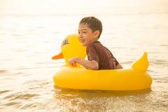 Weinig jongenszitting op het strandgezicht kijkt gelukkig Stock Afbeeldingen
