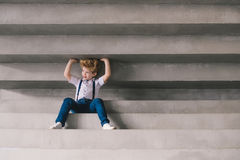 Weinig jongenszitting op staors Stock Foto