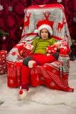 Weinig jongenszitting op stoel dichtbij Kerstmisboom stock foto