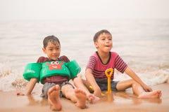 Weinig jongenszitting samen op het strand stock foto