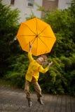 Weinig kameraad vliegt over de werf met een gele in hand paraplu Stock Afbeeldingen