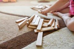 Weinig Kaukasisch meisje zit op tapijt en speelt ontwikkelingsspel, houten speelgoed stock foto