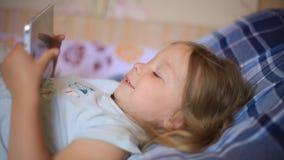 Weinig Kaukasisch twee-jaar-oud meisje die op een plaid hoofdkussen en het letten op beeldverhalen op een tabletcomputer liggen M stock video