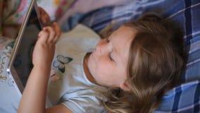 Weinig Kaukasisch twee-jaar-oud meisje die op een plaid hoofdkussen en het letten op beeldverhalen op een tabletcomputer liggen M stock videobeelden