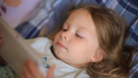 Weinig Kaukasisch twee-jaar-oud meisje die op een plaid hoofdkussen en het letten op beeldverhalen op een tabletcomputer liggen M stock footage