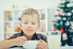Weinig Kaukasische jongen die ontbijt op de vooravond van het nieuwe jaar eten Kerstboom op de achtergrond royalty-vrije stock afbeelding