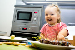 Weinig kind belangrijkste kokende koekjes in de keuken stock foto's