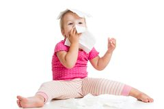 Weinig kind blaast neus terwijl het zitten op die vloer, over wit wordt geïsoleerd stock foto's