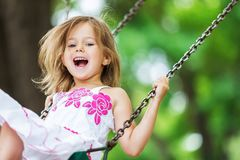 Weinig kind blond meisje die pret op een schommeling hebben stock foto's
