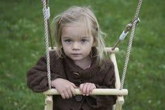 Weinig kind blond meisje die pret op een schommeling hebben openlucht Stock Foto
