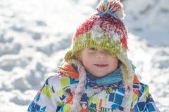 Weinig kind dat in de sneeuw speelt Stock Foto's