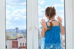 Weinig kind dat door het vensterglas kijkt royalty-vrije stock foto