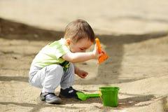 Weinig kind dat in zandbak speelt Stock Afbeeldingen