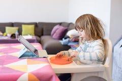Weinig kind die als hoge voorzitter met digitale tablet eten Stock Fotografie